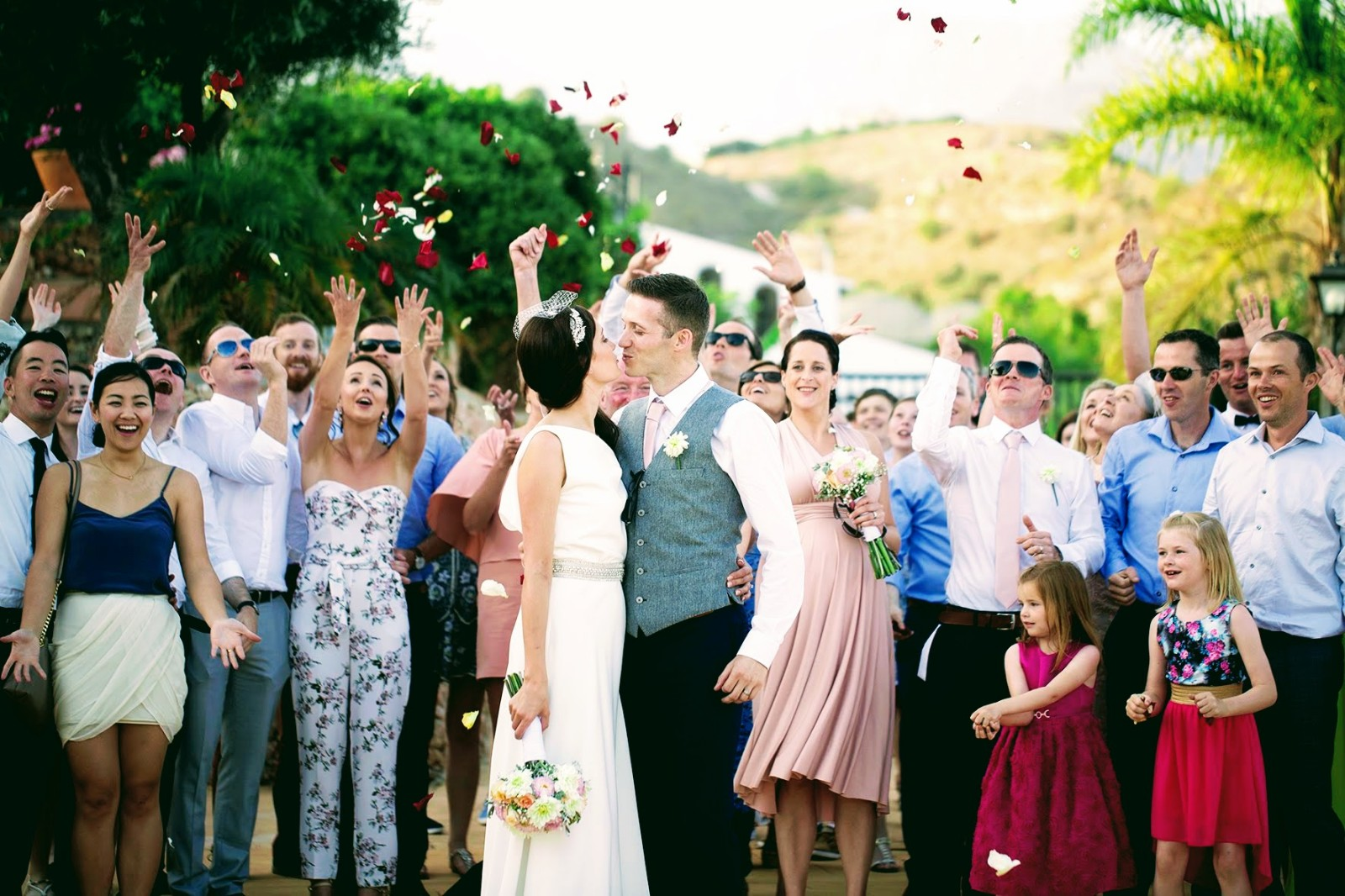 Family throwing petals to couple
